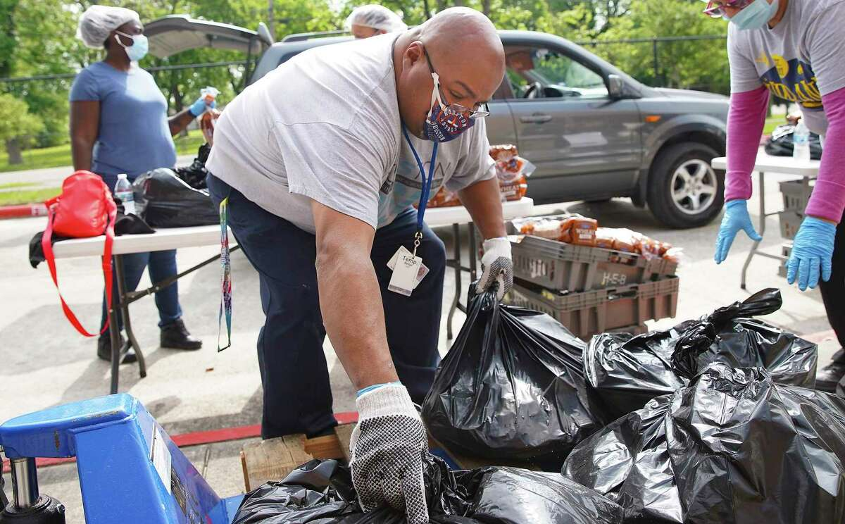 Houston ISD employee José Hernandez grabs bags of food to distribute to families in front of Wesley Elementary Schoool on Monday, April 6, 2020. District officials said they provided 500 boxes of food at the campus on Houston's northwest side.