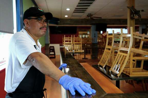 Enrique Torres, co-owner of The Mesquite Grill, looks out the front window of The Mesquite Grill on Monday, April 6, 2020, in Houston. On Tuesday, Harris County Commissioners Court is working to approve a $10 million small business loan fund to help business hurt by the COVID-19 pandemic. The restaurant opened February 29 of this year, a week and a half later they had to close the dinning room and only take to-go orders due to the pandemic.