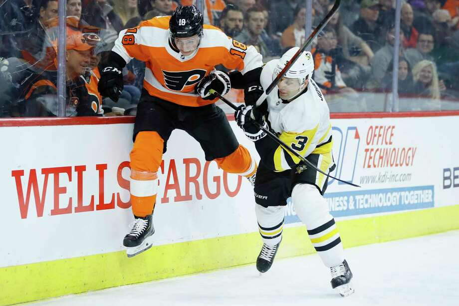 FILE - In this Jan. 21, 2020, file photo, Philadelphia Flyers' Tyler Pitlick, left, tries to jump past Pittsburgh Penguins' Jack Johnson during the second period of an NHL hockey game in Philadelphia. The latest chapter of The Battle of Alberta is on hold. So's the potential renewal of the Pennsylvania rivalry between the Penguins and Flyers. It's unclear when or if the coronvirus pandemic-delayed NHL playoffs -- which were supposed to begin Wednesday -- will be played or what form they'll resemble. (AP Photo/Matt Slocum, FIle) / Copyright 2020 The Associated Press. All rights reserved