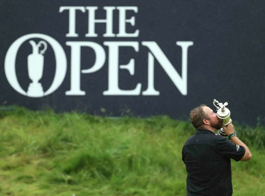 FILE - In this Sunday, July 21, 2019 file photo Ireland's Shane Lowry holds and kisses the Claret Jug trophy on the 18th green as he poses for the crowd and media after winning the British Open Golf Championships at Royal Portrush in Northern Ireland. The organizers of the British Open announced Monday April 6, 2020, that they have decided to cancel the event in 2020 due to the current Covid-19 pandemic and that the Championship will next be played at Royal St George's in 2021. (AP Photo/Peter Morrison)