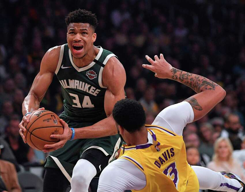 FILE - In this March 6, 2020, file photo, Milwaukee Bucks forward Giannis Antetokounmpo (34) knocks down Los Angeles Lakers forward Anthony Davis as he drives to the basket during the first half of an NBA basketball game in Los Angeles. Antetokounmpo is spending much of his time during the coronavirus-imposed hiatus working out, helping care for his newborn son and playing occasional video games. What the reigning MVP isna€™t doing very often is shooting baskets now that the NBA has closed down team practice facilities. (AP Photo/Mark J. Terrill, File)