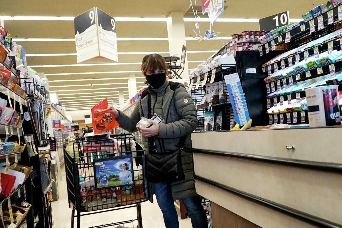 A customer wears a mask as she shops at a Jewel Osco grocery store in Mount Prospect, Ill., Saturday, April 4, 2020. The Centers for Disease Control and Prevention (CDC) now recommends Americans consider wearing cloth or fabric face covering in public spaces such as grocery stores and public transit stations to help slow the spread of the coronavirus. (AP Photo/Nam Y. Huh)
