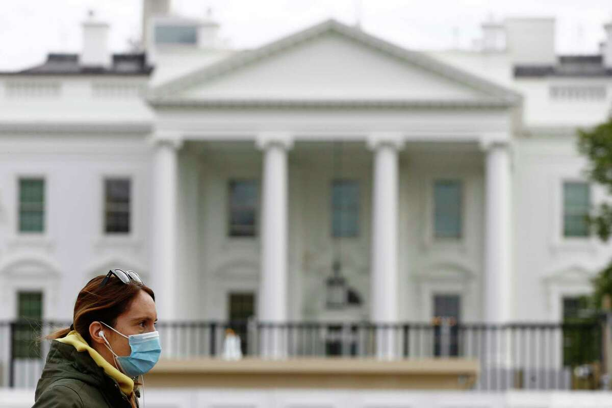 FILE - In this April 1, 2020, file photo a woman wearing a face mask walks past the White House in Washington. (AP Photo/Patrick Semansky, File)