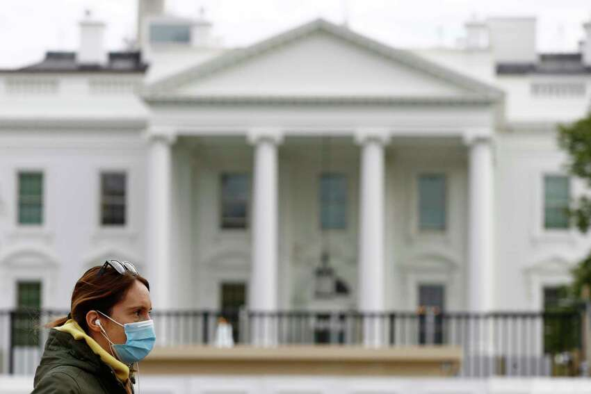 FILE - In this April 1, 2020, file photo a woman wearing a face mask walks past the White House in Washington. Americans are increasingly taking preventative measures, including staying away from large crowds and avoiding touching their hands to their faces, amid growing fears of infection with COVID-19, a new poll from The Associated Press-NORC Center for Public Affairs Research found. (AP Photo/Patrick Semansky, File)