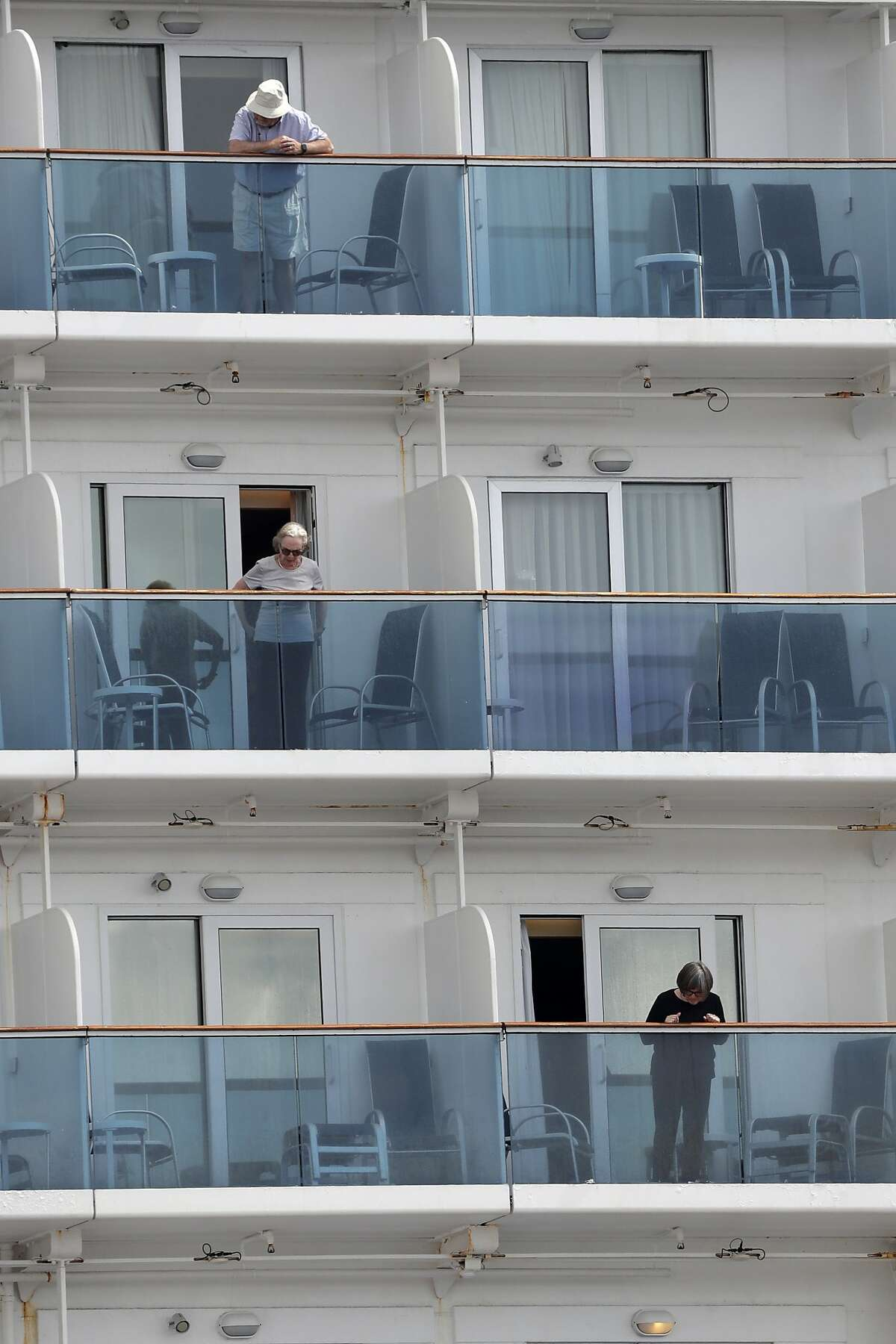 Passengers look out from their balconies on the Coral Princess cruise ship while docked at PortMiami during the new coronavirus outbreak, Monday, April 6, 2020, in Miami. According to Princess Cruises, disembarkation of guests is expected to take several days due to limited flight availability. (AP Photo/Wilfredo Lee)