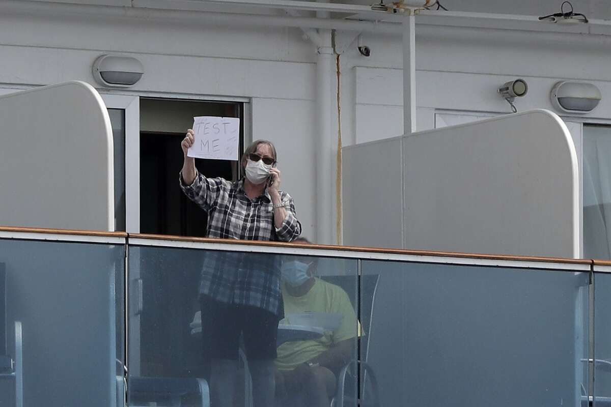 """A passenger wearing a protective mask holds up a sign that reads, """"Test Me,"""" as she stands on the balcony of the Coral Princess cruise ship while docked at PortMiami during the new coronavirus outbreak, Monday, April 6, 2020, in Miami. According to Princess Cruises, disembarkation of guests is expected to take several days due to limited flight availability. (AP Photo/Wilfredo Lee)"""