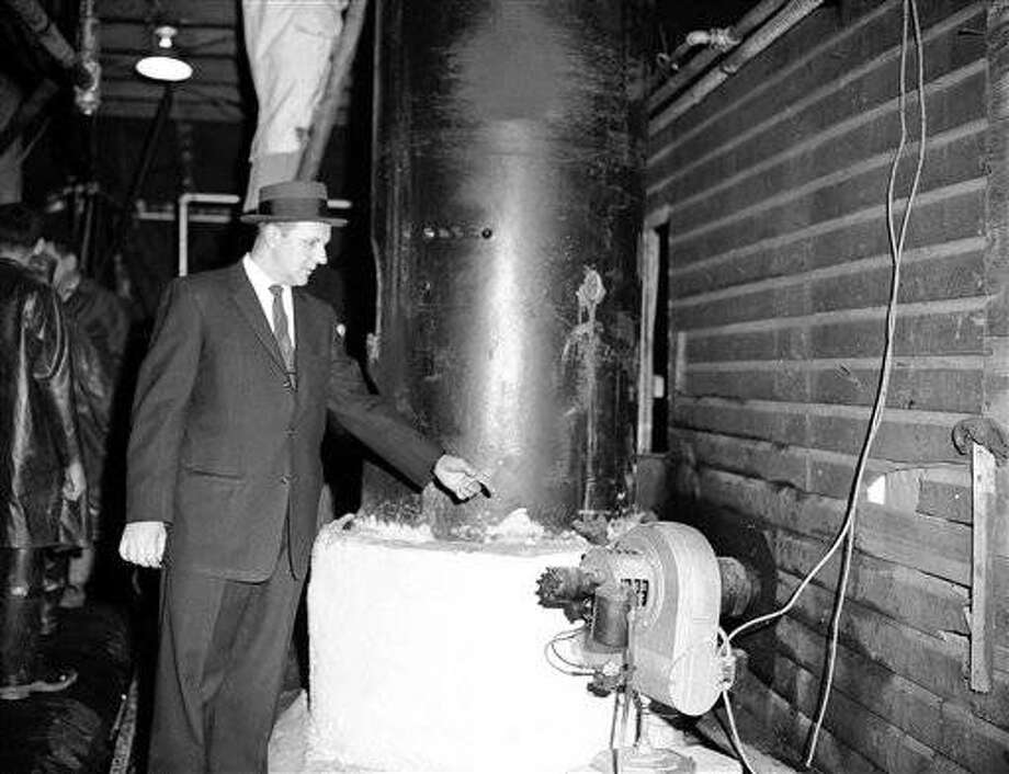 Police said neighbors of Michael Curcio, Saddle Brook, N.J., didnt know he was cooking bootleg whiskey in his garage at night. Here local Police Commissioner Ben Walenczyk points to oil burner under part of the 750-gallon-a-day apparatus after raid on April 7, 1959. In addition to still, they said, Curcio, had four 5,000 gallon mash vats and quantities of bootleg alcohol. (AP Photo)