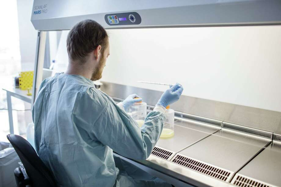 A Copenhagen University researcher works on a potential coronavirus vaccine in March 2020. On April 6, Danbury-based Iqvia Holdings announced an online tool to match patients afflicted with the virus with clinical research and trials under way. Photo: THIBAULT SAVARY / AFP Via Getty Images / AFP or licensors