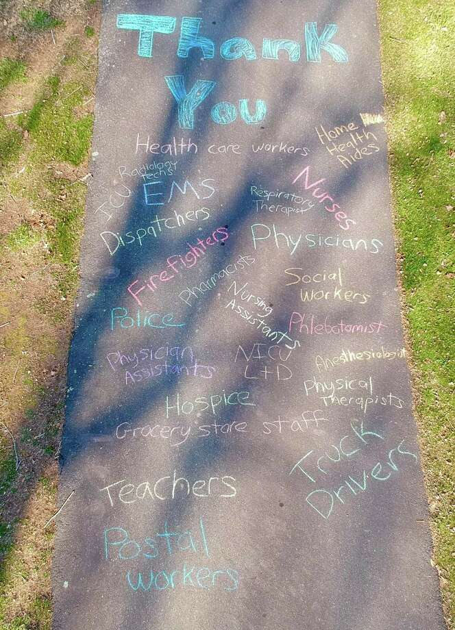 The daughter of Haddam Neck resident Neal Perron, Dharma Perron, a nursing student at The University of Vermont, chalked a message in their driveway thanking first responders for their efforts to combat coronavirus. The list includes teachers, mail carriers and grocery store staff. Photo: Courtesy Neal Perron Photography