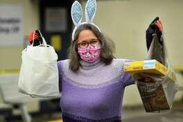 Decked out in festive Easter Bunny ears, Remy Kocurek, director of St. Vincent DePaul of the Valley, collects food donations at the food pantry at 237 Roosevelt Drive in Derby, Conn. on Sunday, April 5, 2020. The pantry has been accepting new clients in the wake of the coronavirus pandemic.