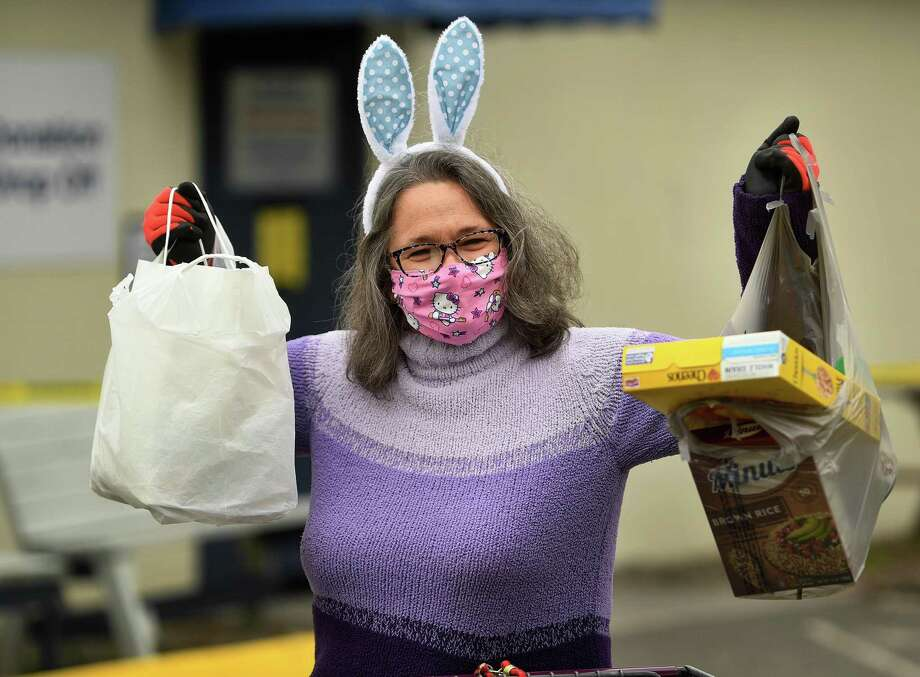 Decked out in festive Easter Bunny ears, Remy Kocurek, director of St. Vincent DePaul of the Valley, collects food donations at the food pantry at 237 Roosevelt Drive in Derby, Conn. on Sunday, April 5, 2020. The pantry has been accepting new clients in the wake of the coronavirus pandemic. Photo: Brian A. Pounds / Hearst Connecticut Media / Connecticut Post