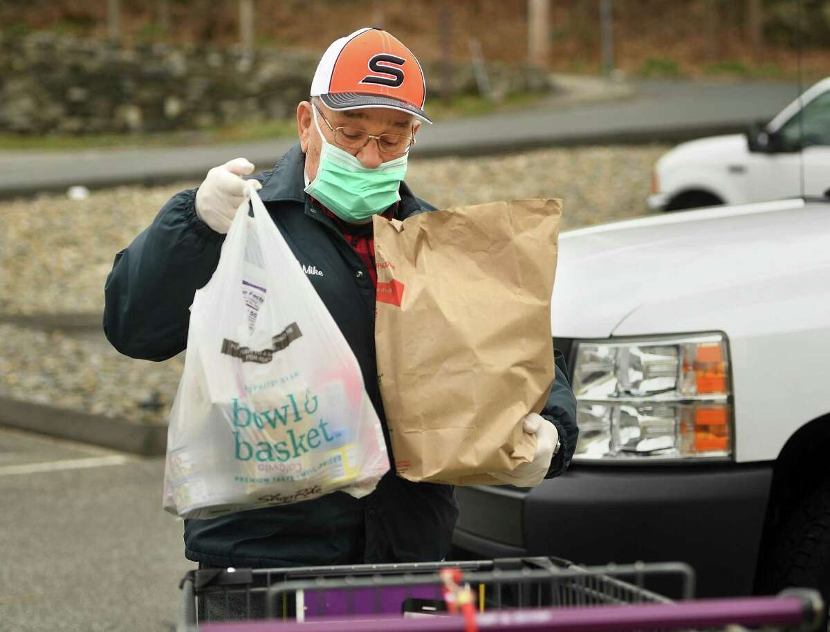 Mike Dokla, of Shelton, donates bags of food to the St. Vincent DePaul of the Valley Food Pantry at 237 Roosevelt Drive in Derby, Conn. on Sunday, April 5, 2020. The pantry has been accepting new clients in the wake of the coronavirus pandemic.