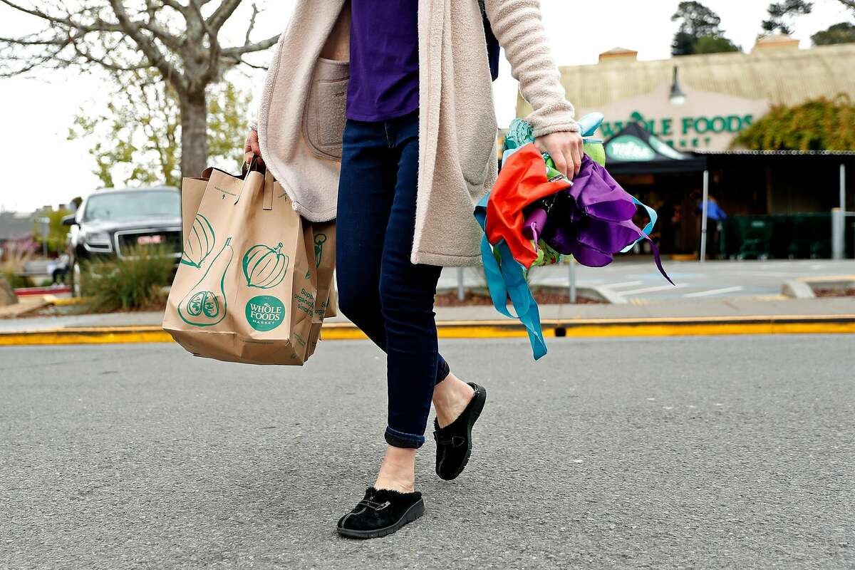 After not being able to use her own bags, a shopper walks across Evergreen Avenue after shopping at Whole Foods in Mill Valley, Calif., on Monday, April 6, 2020.