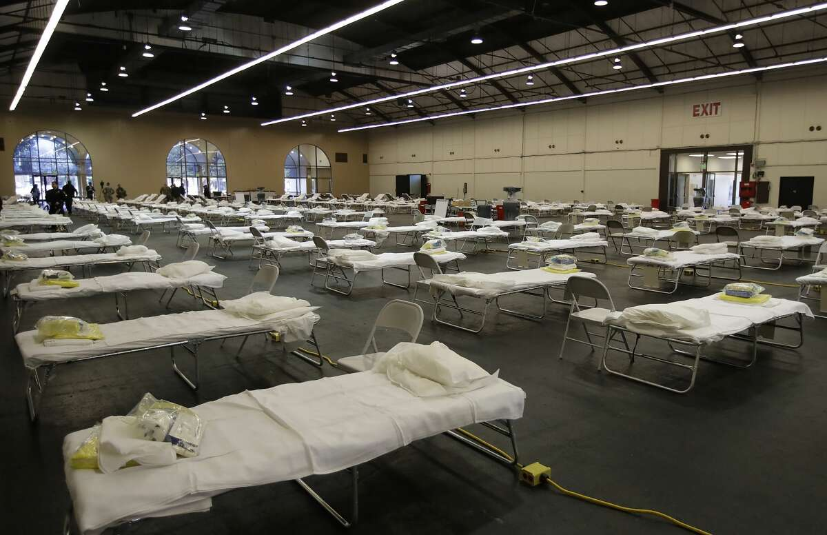 In this April 1, 2020, file photo, cots are set up at a possible COVID-19 treatment site in San Mateo, Calif.
