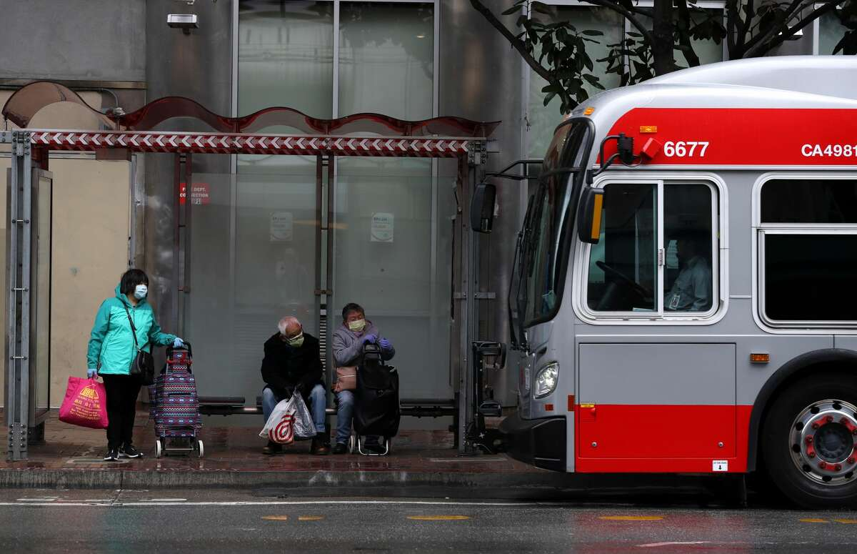 People wear masks as they wait in a bus shelter for a San Francisco MUNI bus during the coronavirus (COVID-19) pandemic on April 06, 2020 in San Francisco, California. The San Francisco Municipal Transportation Agency (SFMTA) announced that they are cutting service to a majority of their 89 bus lines in the City of San Francisco as ridership plummets due to the coronavirus shelter in place.