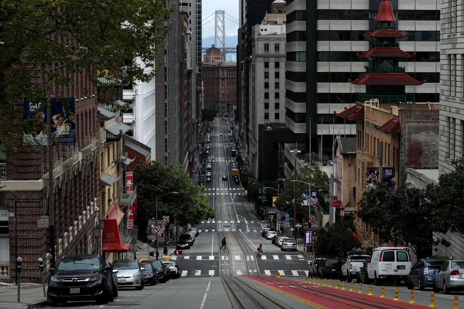 A pedestrian crosses an empty California Street during the coronavirus (COVID-19) pandemic on April 6, 2020 in San Francisco. Residents in the San Francisco Bay Area are continuing to shelter in place due to the coronavirus. Photo: Justin Sullivan/Getty Images / 2020 Getty Images