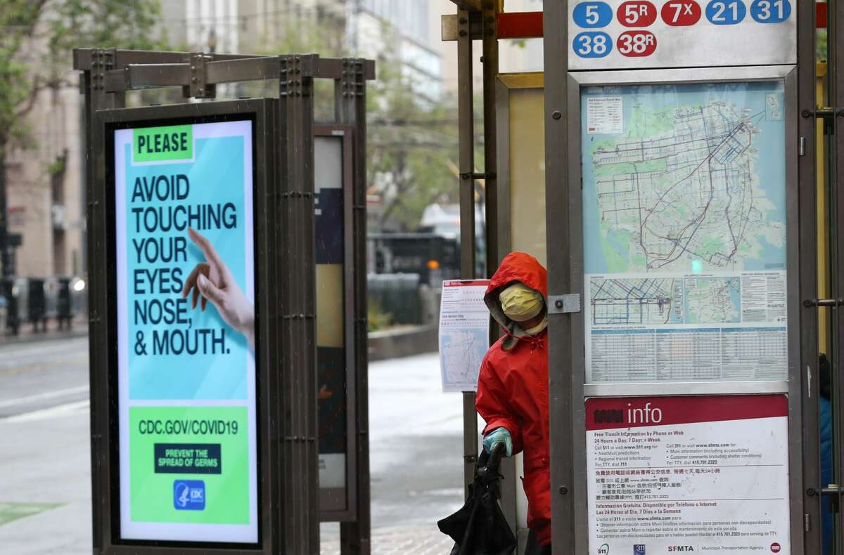A passenger wears a protective mask while waiting for a San Francisco MUNI bus during the coronavirus (COVID-19) pandemic on April 06, 2020 in San Francisco, California. The San Francisco Municipal Transportation Agency (SFMTA) announced that they are cutting service to a majority of their 89 bus lines in the City of San Francisco as ridership plummets due to the coronavirus shelter in place.