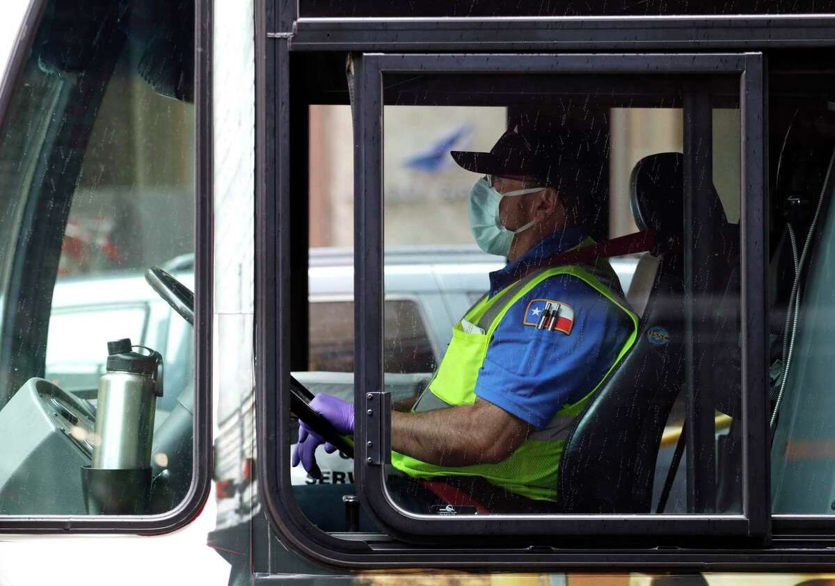 A VIA bus driver wears a protective mask and gloves as he drives through downtown San Antonio on March 30, 2020. VIA will give riders until Wednesday before enforcing the city and county's order to wear masks in public places. (AP Photo/Eric Gay)