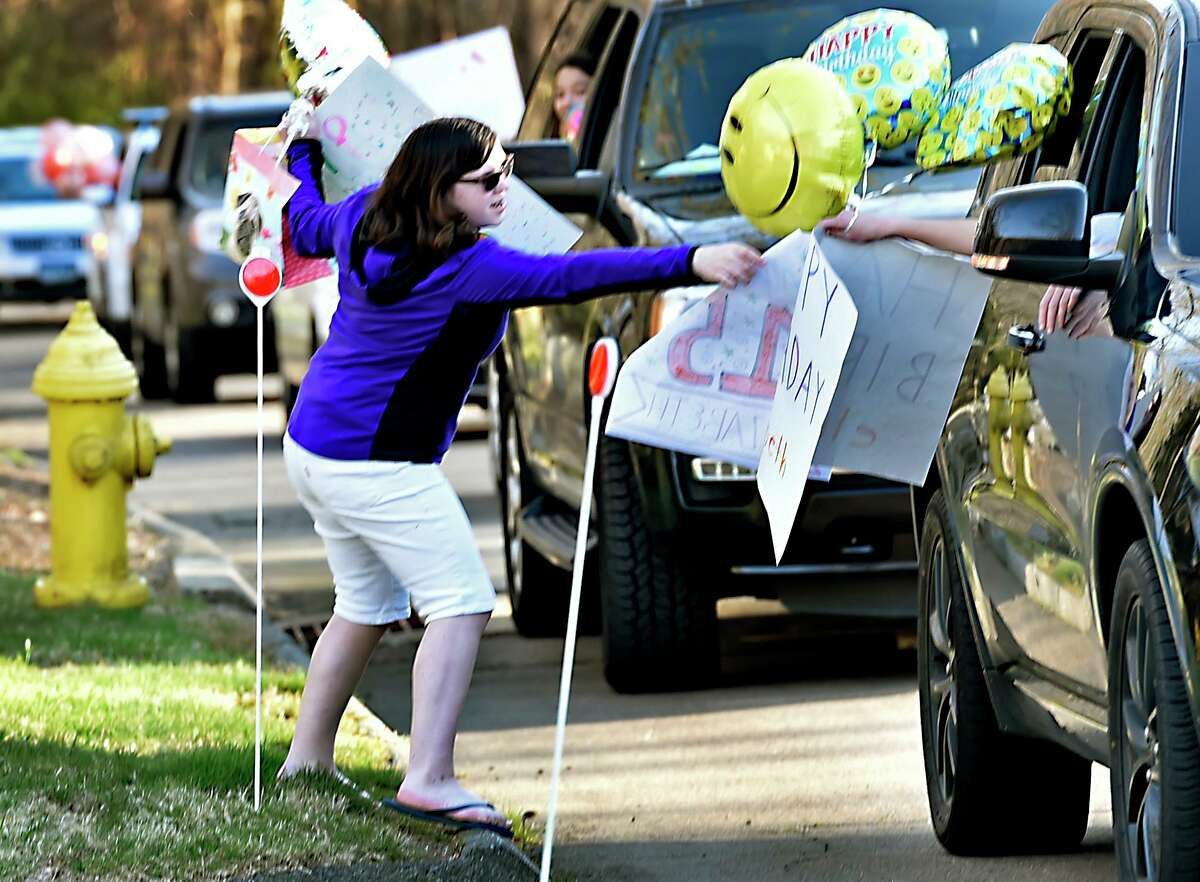 Elizabeth Romanovsky, 15, is given a happy birthday sign and gallons during a surprise parade of cars slowly driving by her Orange home on Green Circle Road celebrating her 15th birthday April 06, 2020 in lieu of a party to comply with the social distancing protocol during the coronavirus pandemic.