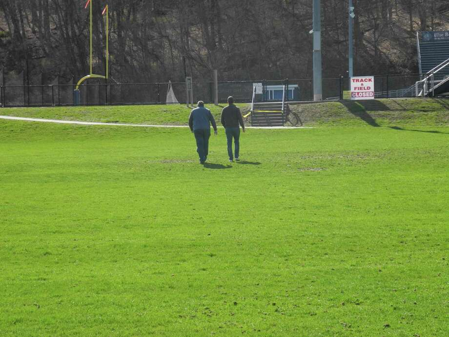 Two men walk across a field at Wilton High School toward the path that leads to Cider Mill School. People caught using closed recreational facilities face a $92 trespassing fine. Photo: Jeannette Ross / Hearst Connecticut Media / Wilton Bulletin