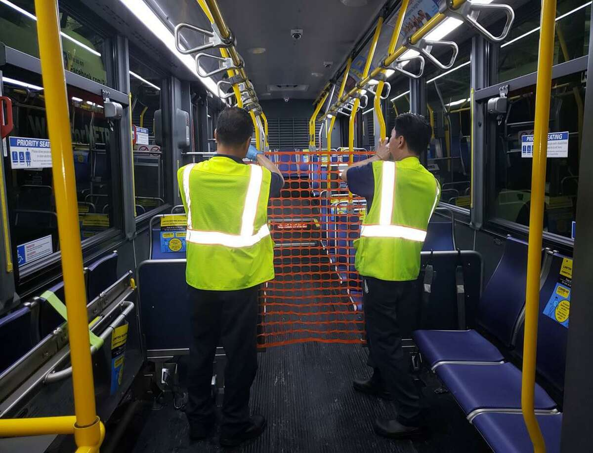 Workers install a net barrier between seats on a Metropolitan Transit Authority bus. The netting separates most passengers from the bus driver, while leaving room for elderly and disabled passengers to sit in the front of the bus. Other passengers board from the back door of the bus.