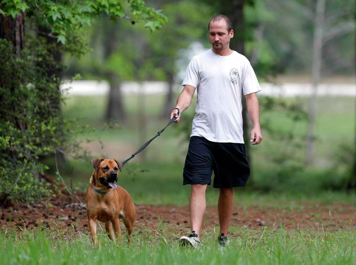 Andrew Grass walks his one-year-old Black Mouth Cur at William Goodrich Jones State Forest. Grass said he walks his dog up to two times a day at the park to get his dog's energy out. Governor Greg Abbott anounced Tuesday all state parks, including Jones State Forest, would be closed to minimize the spread of the new coronavirus.