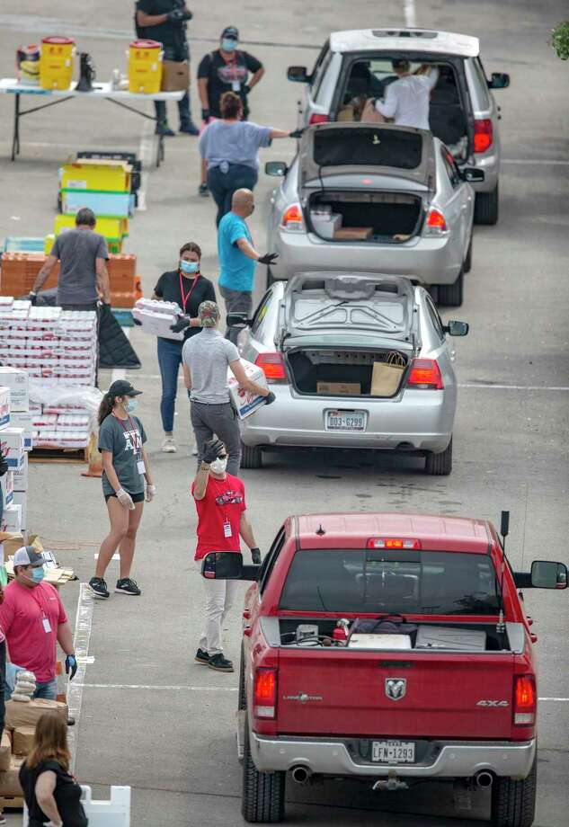 Food Bank volunteers practice social distancing while distributing food at Toyota Field earlier this month. While the pandemic has forced us physically apart, it has also revealed our interconnection. Photo: William Luther /Staff Photographer / ©2020 San Antonio Express-News