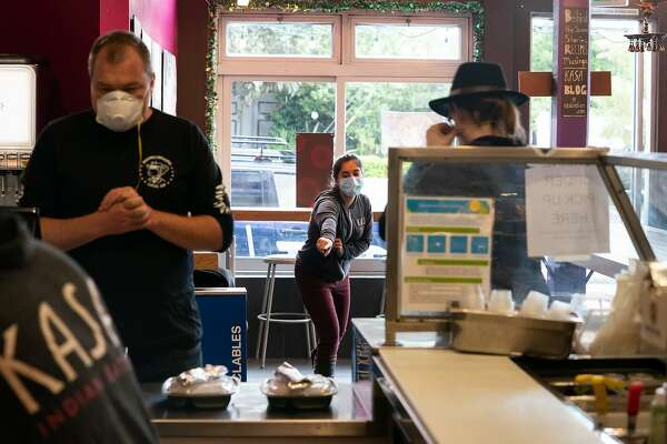 Anamika Khanna, CEO of Kasa Indian Eatery, points to distancing tape to a customer on Monday, April 6, 2020, in San Francisco, Calif.
