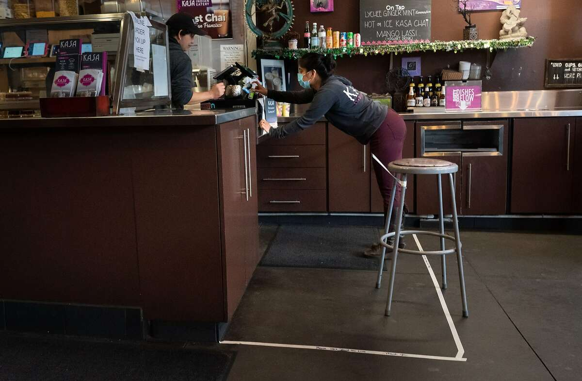 Anamika Khanna, CEO of Kasa Indian Eatery, reaches for some disinfectant gel over marked distancing tape on Monday, April 6, 2020, in San Francisco, Calif.