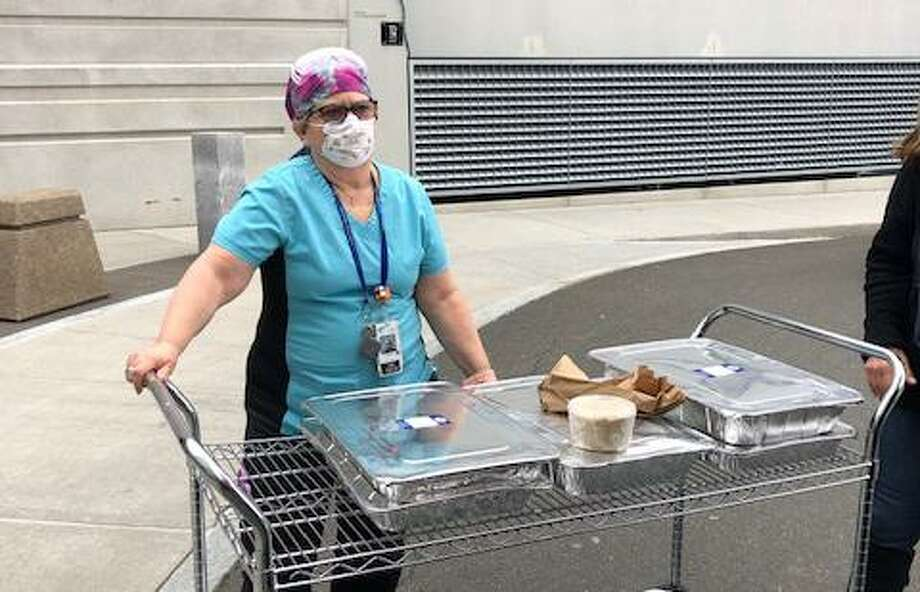 An emergency room nurse at Danbury Hospital accepts lunch for herself and her colleagues donated by the Wilton Warriors' Front Line Appreciation Facebook group. Photo: Contributed Photo / / Wilton Bulletin
