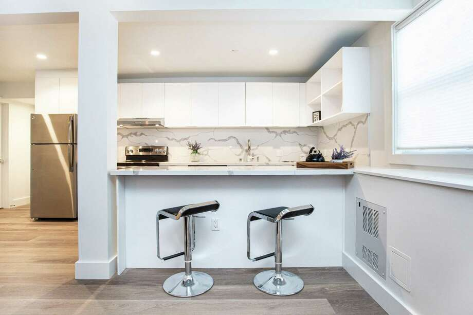High-gloss cabinetry, a stone backsplash and stainless steel appliances outfit this kitchen finished by designer Robin Randall of Veritas Investments. Photo: Veritas Investments
