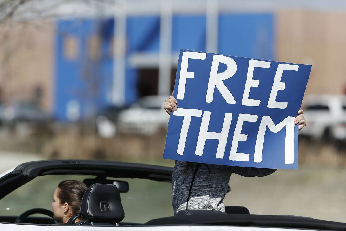 A protester wields a placard while riding in a convertible as members of the groups Abolish ICE Colorado, Sanctuary for All, American Friends Committee and Never Again Action take part in a car protest to call for the release of detained immigrants at the GEO Detention Center, because of the coronavirus, Friday, April 3, 2020, in Aurora, Colo. (AP Photo/David Zalubowski)