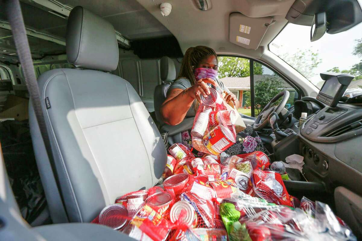 Kids Meals Inc, driver, Susie Bell prepares to hand out canned food as she made her deliveries Tuesday, April 7, 2020, in Houston. Kids Meals Inc, a non-profit that delivers meals to pre-school age children who live in underserved communities.