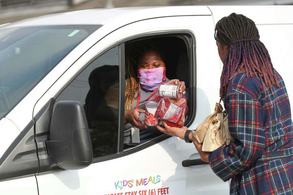 Kids Meals Inc, driver, Susie Bell hand outs canned food and sack lunches as she made her deliveries Tuesday, April 7, 2020, in Houston. Kids Meals Inc, a non-profit that delivers meals to pre-school age children who live in underserved communities.