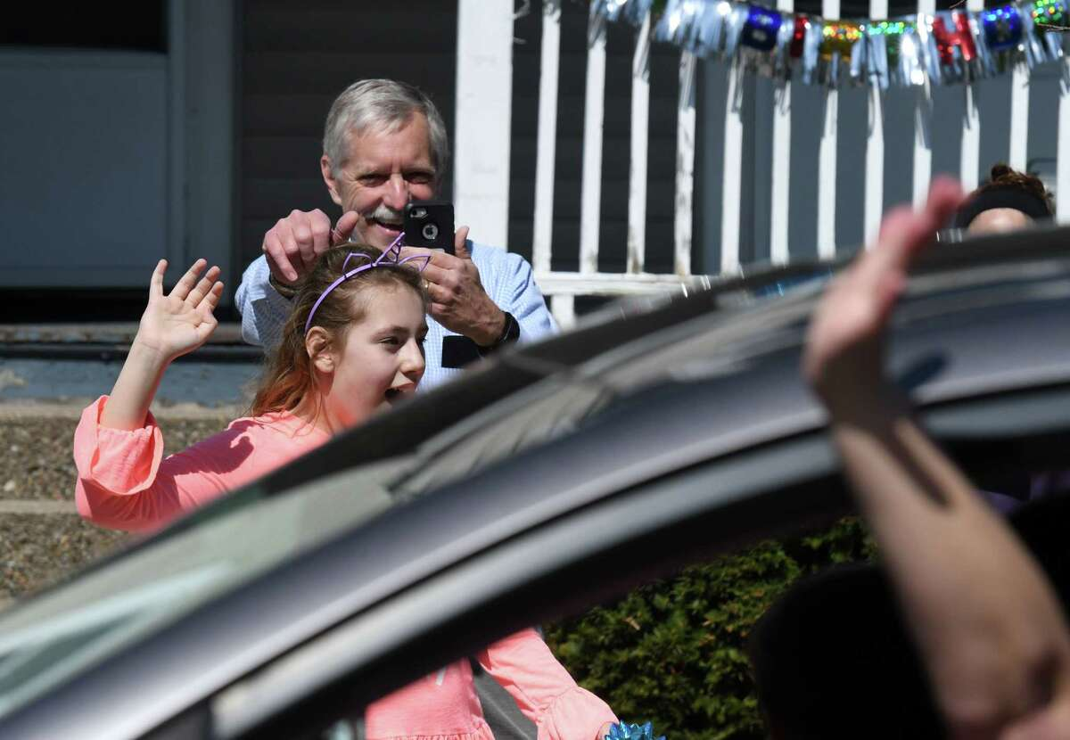 Annabelle Carroll, who suffers from autism, is delighted at the sight of a surprise parade thrown by friends and well wishers to celebrate her eleventh birthday on Tuesday, April 7, 2020, on Sycamore Street in Albany, N.Y. An Albany fire truck and several Albany police cars led the parade. (Will Waldron/Times Union)