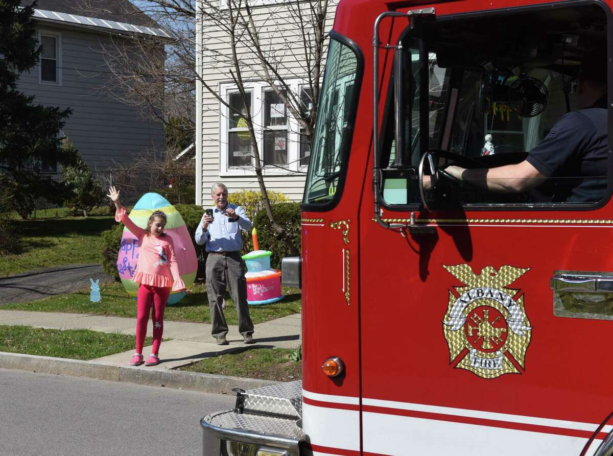 Annabelle Carroll, who suffers from autism, is delighted at the sight of surprise parade thrown by friends and well wishers to celebrate her eleventh birthday on Tuesday, April 7, 2020, on Sycamore Street in Albany, N.Y. An Albany fire truck and several Albany police cars led the parade. (Will Waldron/Times Union)
