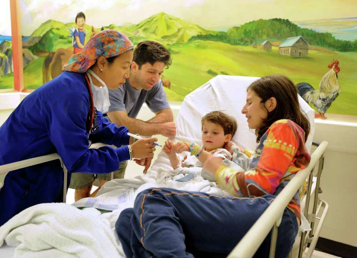 Dr. Mercy Lagmay, left, talks with Aaron Weinbach, 5, and his parents, Michael and Bonnie, just before surgery in pre-op Wednesday, August 18, 2010.