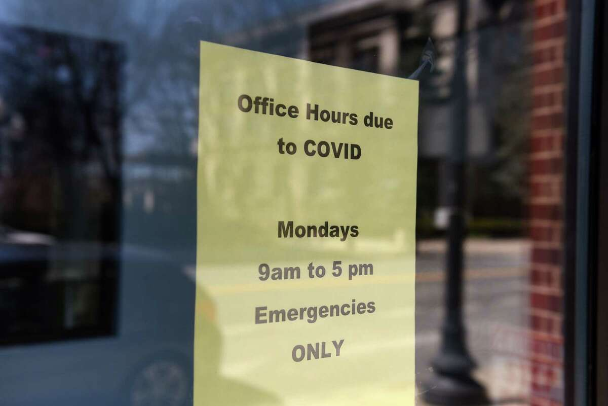 A sign in the door of Albany Upstate Dental alerts patients of new business hours during the coronavirus lockdown on Tuesday, April 7, 2020, in Albany, N.Y. (Will Waldron/Times Union)