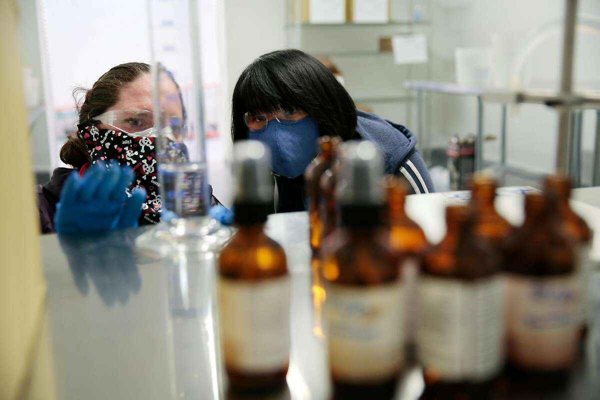 Cheriene Griffith, director of operations, left, and cannabis baker Dan Nguyen demo a dry run of hand sanitizer production at The Galley cannabis production facility in Santa Rosa, California, Tuesday, April 7, 2020. The company is responding to the COVID-19 pandemic by starting production of �Stop & Sanitize� hand sanitizer spray in their new production facility. Ramin Rahimian/Special to The Chronicle