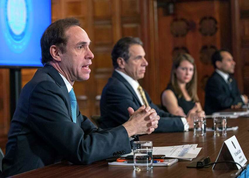 New York State Health Commissioner Howard Zucker, left, joins Gov. Andrew Cuomo, center, during a coronavirus update press conference on Tuesday, April 7, 2020, in the Red Room at the Capitol in Albany, N.Y.