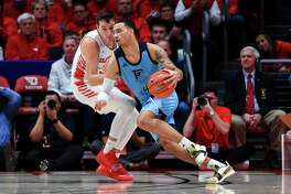Dayton's Ryan Mikesell (33) defends as Rhode Island's Tyrese Martin (4) controls the ball in the first half of an NCAA college basketball game, Tuesday, Feb. 11, 2020, in Dayton, Ohio. Dayton won 81-67. (AP Photo/Aaron Doster)