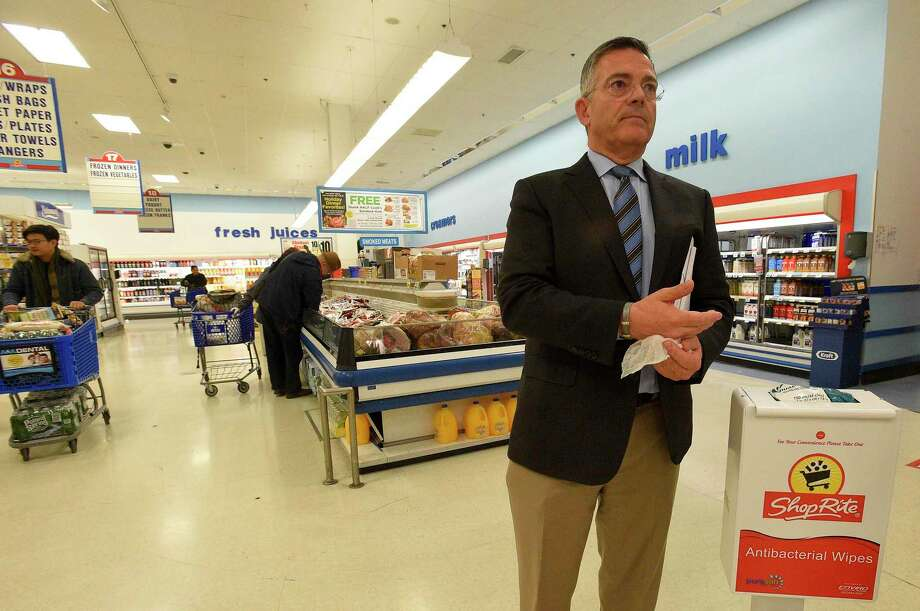 "Tom Cingari, President and Owner of several Shop Rite Food Markets in Stamford and Norwalk, uses a sanitizer wipe to clean his hands as he walks his Stamford, Connecticut store on March 14, 2020. With the outbreak of the COVID-19 Coronavirus, Cingari and his staff have taken a pro-active approach, setting up hand sanitizing stations through out the store for customers to use. Providing protecting gloves for use by staff as well as customers. Cleaning ""Touch Points"" more frequently, such as areas around their Hot and Cold Buffet stations, changing out serving spoons and wiping down surfaces throughout the store, in an attempt to limit customer exposure to the coronavirus while they shop. Although some shelves are empty, the store is receiving daily shipments and products are being put out as soon as they are received. Photo: Matthew Brown / Hearst Connecticut Media / Stamford Advocate"