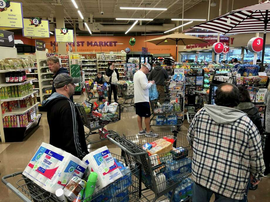 Customers wait in line in mid-March 2020 at a Big Y supermarket in Saugus, Mass. The company is closing all Massachusetts and Connecticut stores on Easter Sunday and the following day on Monday, April 13, to give its employees a respite during the crush of business spurred by people stocking up on supplies as they wait out the COVID-19 pandemic. Photo: ERIC BARADAT / AFP Via Getty Images / AFP or licensors