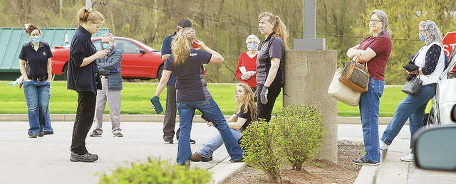 Aldi customers visit with employees of the Alton store Tuesday morning as Ameren workers stopped a natural gas leak at the rear of the building. About 20 customers reportedly were in the store at the time of the gas line break. Photo: John Badman | The Telegraph