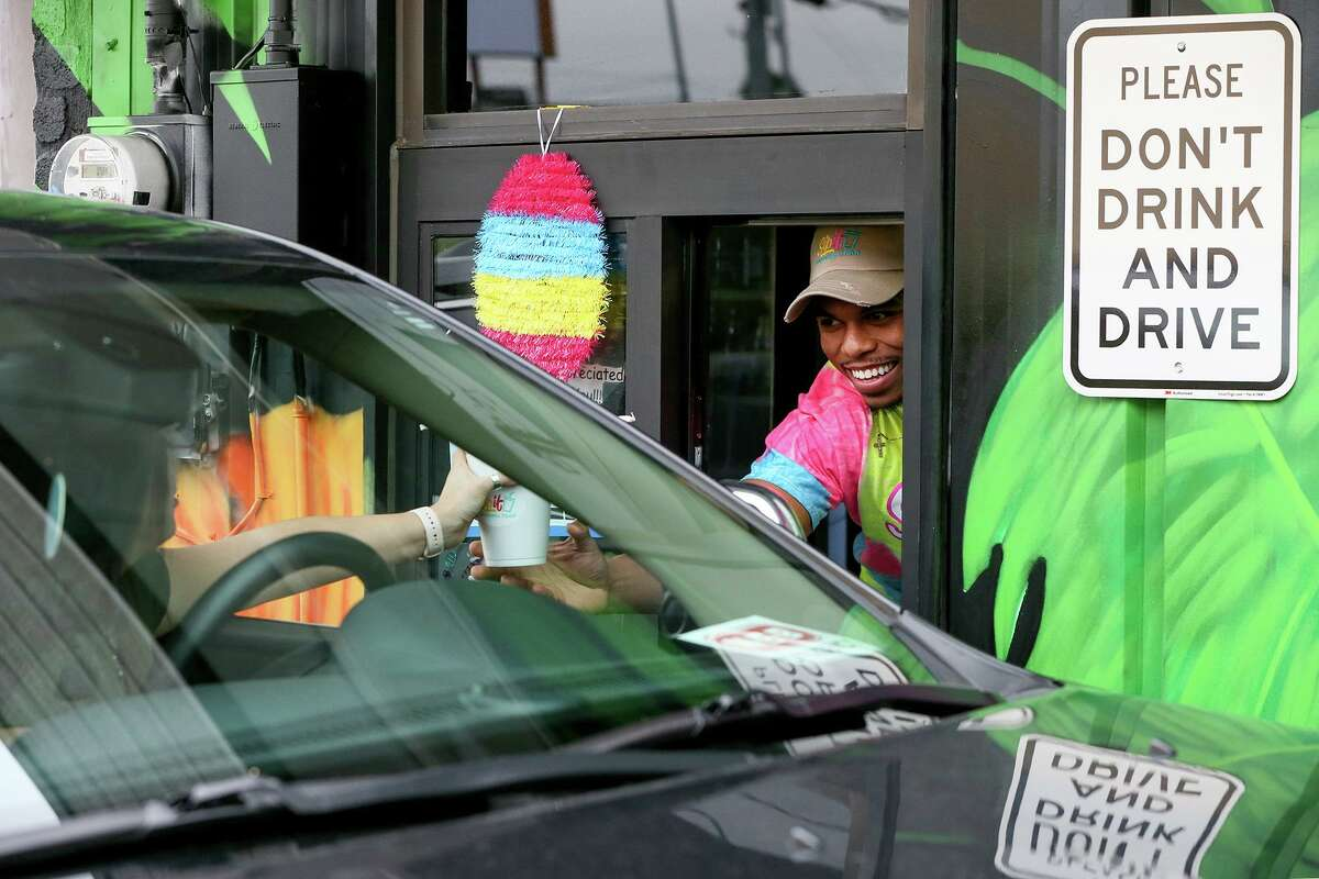 Owner Bernardo Baxter serves a frozen daiquiri to a customer in the drive-thru lane at SipIt Daiquiris To-Go, 1717 Pat Booker Road in Universal City, on Sunday.
