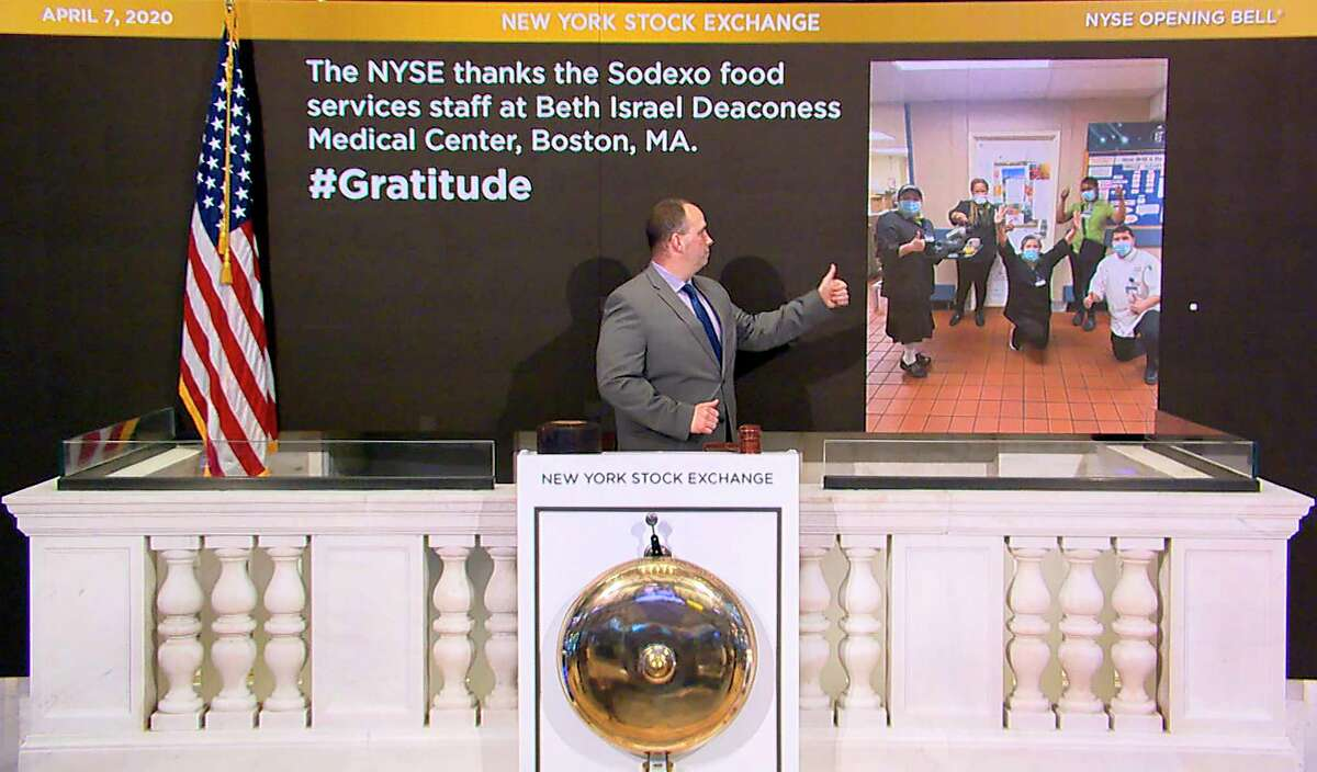 In this image taken from video provided by the New York Stock Exchange, Tommy Gannon, Assistant Supervisor, Facilities, rings the opening bell at the NYSE, and recognizes the Sodexo food services staff at Beth Israel Deaconess Medical Center in Boston, Tuesday, April 7, 2020, in New York. (New York Stock Exchange via AP)