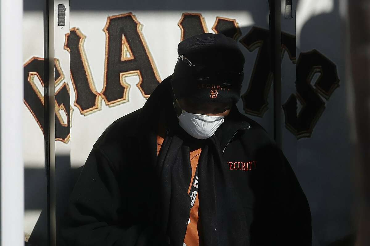 Security guard LeJuana Evans wears a mask while working a gate at Oracle Park, the San Francisco Giants' baseball ballpark, in San Francisco, Thursday, March 26, 2020. There will be empty ballparks on what was supposed to be Major League Baseball's opening day, with the start of the Major League Baseball regular season indefinitely on hold because of the coronavirus pandemic. (AP Photo/Jeff Chiu)