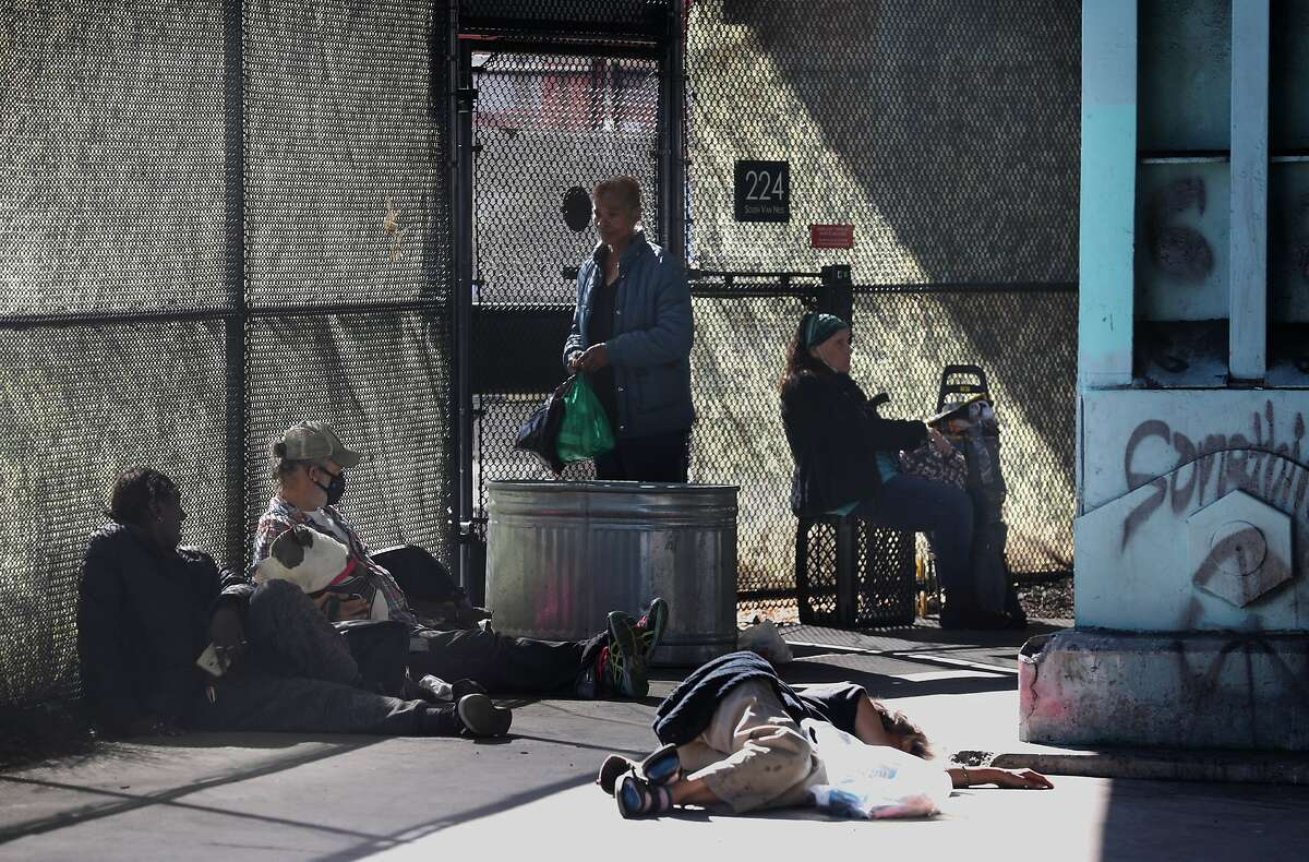 There is a wait outside the gated entrance of the Division Ccircle Navigation Center on South Van Ness ave. where there is a first positive COVID-19 diagnosis of a homeless person in a shelter seen on Thursday, April 2, 2020, in San Francisco, Calif.