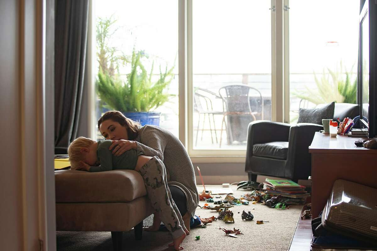 Izabel Arnold, 26, comforts her three-year-old son Arlo at home on Saturday, March 28, 2020, in San Francisco, Calif.