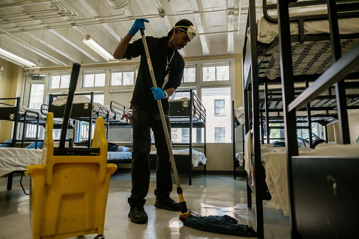 Cliff Bonnet cleans the floors of the dormitory quarters of Hospitality House, a men's homeless shelter in the Tenderloin in San Francisco, Calif. on Tuesday April 7, 2020. Bonnet, formerly a resident of the shelter is now the facility's janitor.